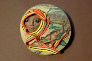 "The Gift, immigration, polymer clay on wood disk 6"" diameter. $40"